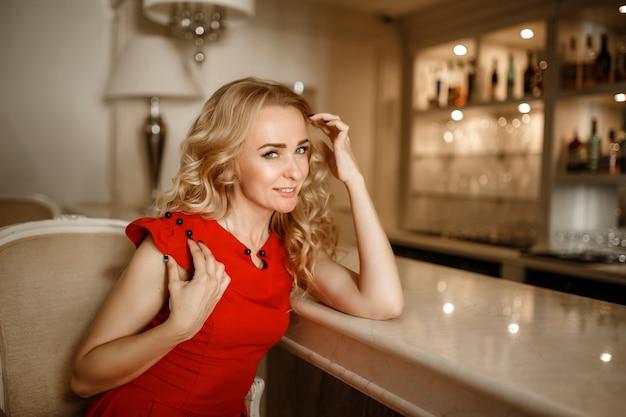 豪華なインテリアで魅惑的なブロンド。ホテルの別荘のアパートで健康的な光沢のある髪のセクシーなドレスを着たスタイリッシュでリッチなスリムな女の子。休暇リゾートの春夏のファッショングラマラスショット