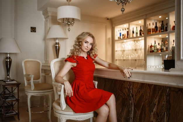 Alluring blonde in luxury interior. stylish rich slim girl in sexy dress with healthy glossy hair at hotel villa apartment. fashion glamorous shot at vacation resort spring-summer