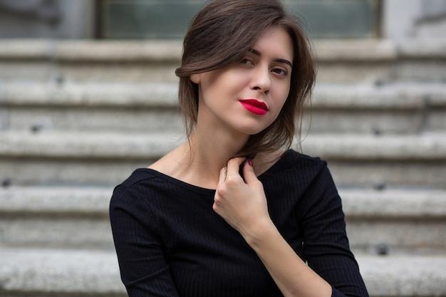 赤い唇を持つ魅力的なブルネットの女性は、灰色のコンクリートの階段に座っている黒いドレスを着ています