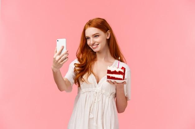 白いドレスに赤い長い髪の魅力的な白人の誕生日の女の子