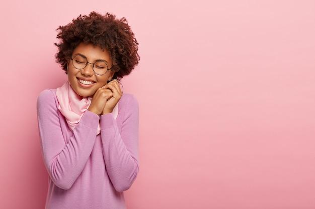 アフロの髪型で魅力的な幸せな女性は、楽しくニヤリと笑い、積極性を表現し、喜びから目を閉じ、心地よい笑顔を持ち、透明なメガネとセーターを着て、バラ色の壁の上のモデルを屋内に置きます
