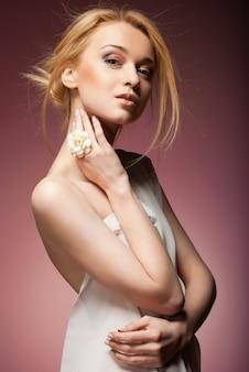흰 천으로 덮인 매혹적인 벌거 벗은 여자. 분홍색 배경 위에 절연