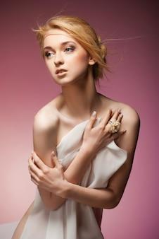 白い布で胸を覆う魅惑的な裸の女性。ピンクの背景に分離
