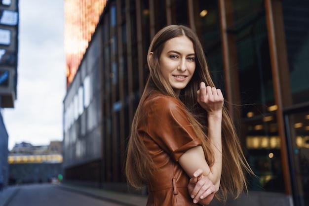 Seducente e impertinente giovane donna caucasica con i capelli lunghi, indossa un abito marrone alla moda, cammina lungo una strada deserta.