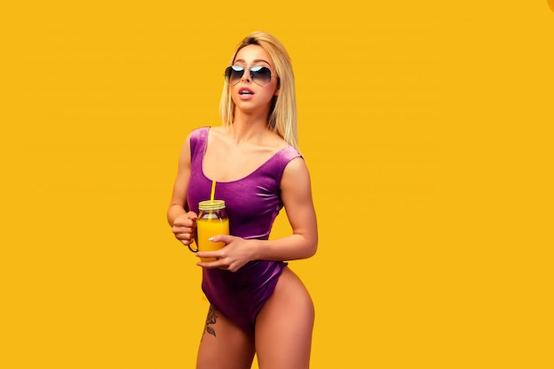 Alluring tattooed model with refreshing drink