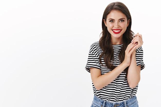 Очаровательная нежная молодая женщина в красной помаде, полосатой футболке, потирая руки, нежно касаясь рук, радостно улыбаясь, счастливо стоит на белой стене