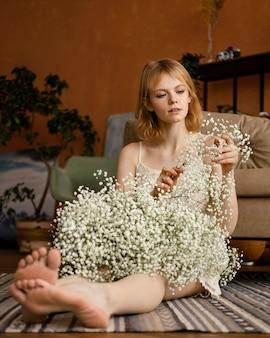 春の花を持ってソファの横でポーズをとる魅力的な女性