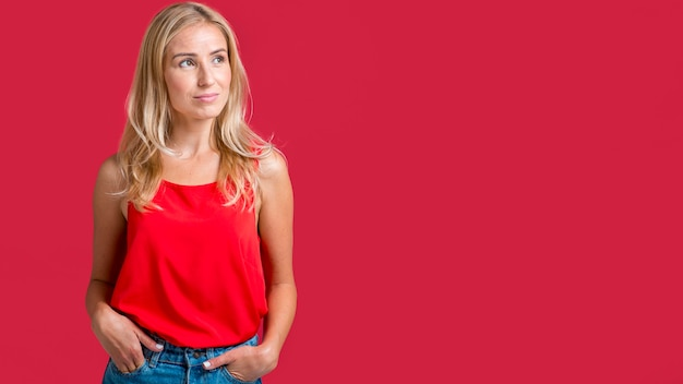 Alluring woman posing in red tank top with copy space