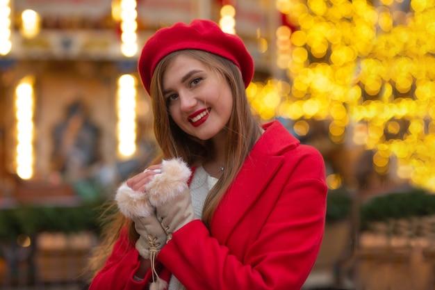ストリートフェアで歩く赤いコートの魅力的な若い女性
