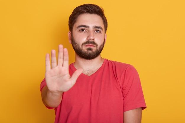 Спокойный бородатый молодой человек в красной повседневной футболке стоит с жестом предупреждения стоп и смотрит в камеру с серьезным лицом