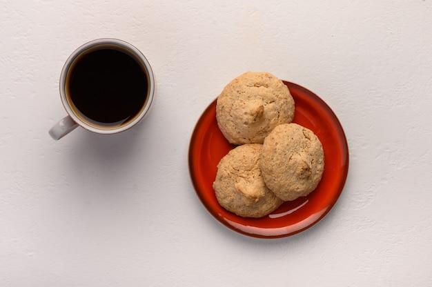 Миндальное печенье на тарелке и чашка чая на светлом фоне.