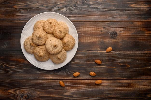 Миндальное печенье на белой тарелке на деревянном фоне.