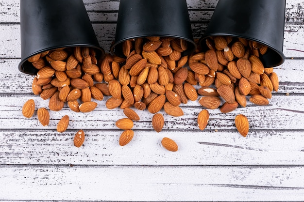 Almond in a black buckets top view on a white wooden table