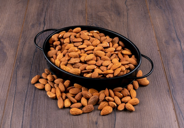 Almond in a black pan high angle view on a white wooden table