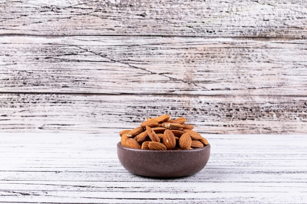 Almond in a bowl side view on a white wooden table