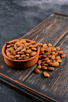 Almond in a bowl and wooden board on a black stone table. high angle view.
