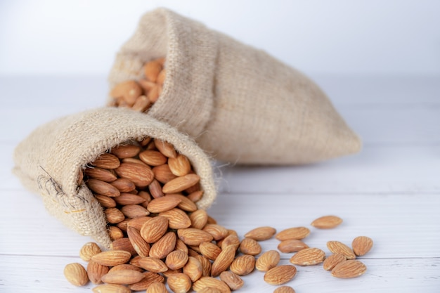 Almond in cloth bag on blurred white table