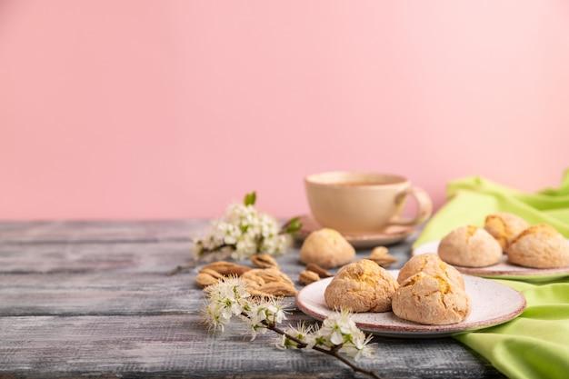 Миндальное печенье и чашка кофе на сером и розовом фоне и зеленой льняной ткани. вид сбоку, крупным планом, выборочный фокус, копией пространства.