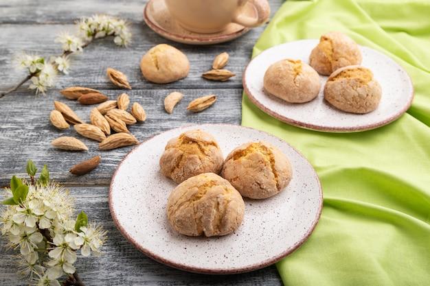 アーモンドクッキーとコーヒーのカップは灰色の木製の背景と緑のリネン繊維。側面図、クローズアップ。