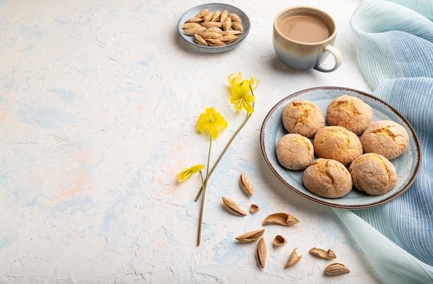 白いコンクリートの背景と青いリネンの織物にアーモンドクッキーと一杯のコーヒー。
