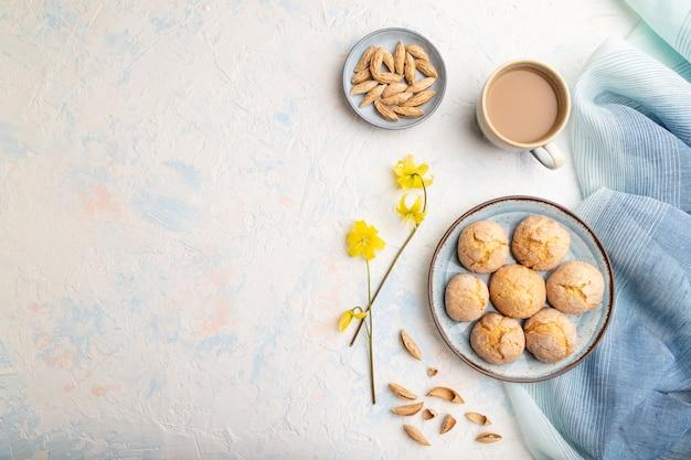 白いコンクリートの表面と青いリネンのテキスタイルにアーモンドクッキーと一杯のコーヒー