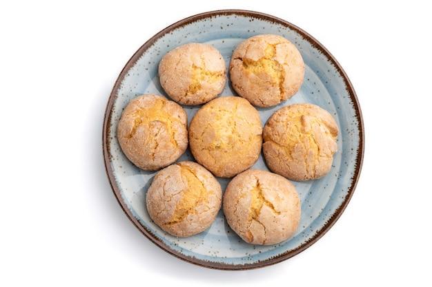 白い表面に分離された青いプレート上のアーモンドクッキー