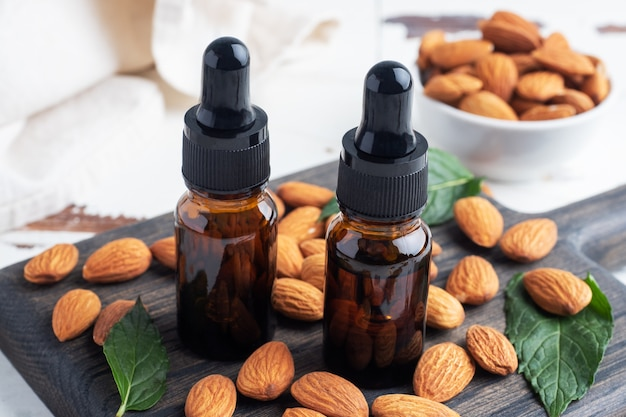 Almond essential oil in dark glass bubbles and fresh almond nuts