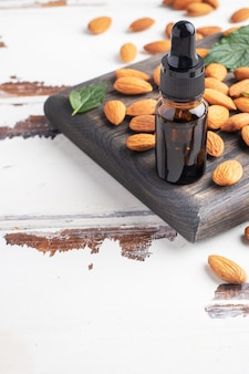 Эфирное масло миндаля в пузырьках из темного стекла и свежие миндальные орехи.