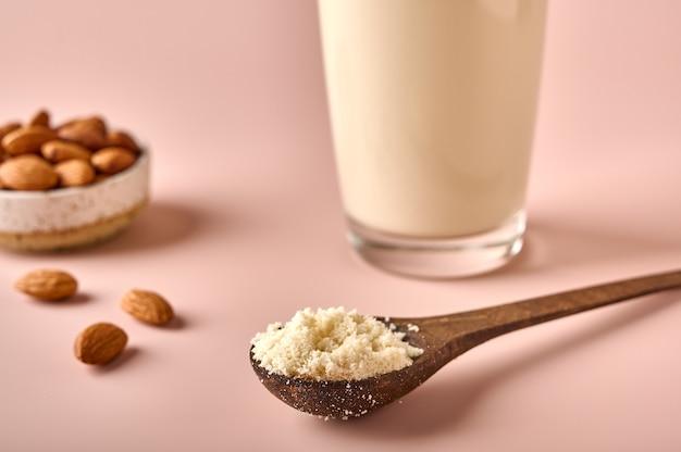 Миндальная мука в деревянной коричневой ложке ореховых ядер и ореховое молоко в стакане на розовом порошковом фоне макроса