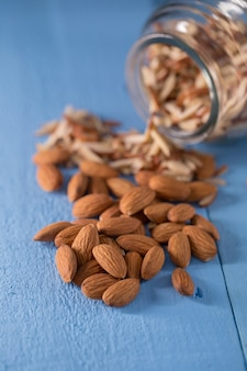 Almond in glass bottle and fresh nuts over blue background
