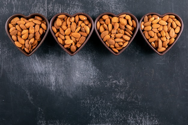 Almond in a heart shaped bowls on a black stone table. top view.