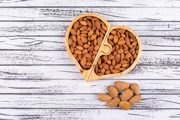 Almond in a heart shaped wooden plate on a white wooden table. top view.