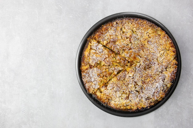 Almond homemade cake with sliced almonds crust and icing powder sugar on light gray concrete surface
