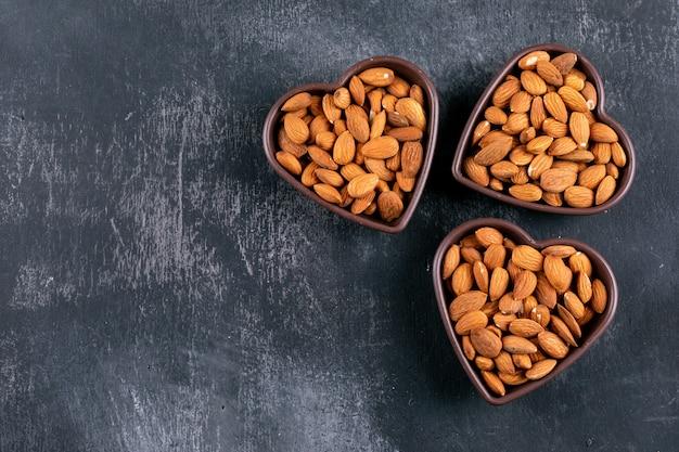 Миндаль в форме сердца чаши на черном каменном столе. плоская планировка