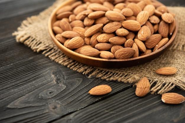 木製のボウルにアーモンド。木製の背景に、黄麻布のバッグの近く。健康食品とスナック、有機菜食主義の食品。