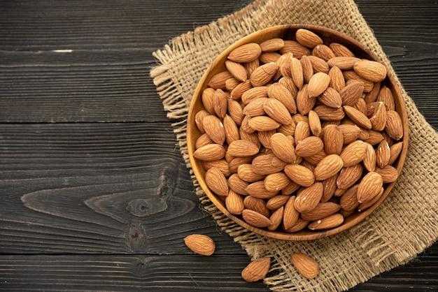 Миндаль в деревянной миске. на деревянном фоне, возле сумки из мешковины. здоровое питание и закуски, органическое вегетарианское питание.