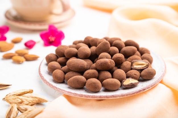 Миндаль в шоколадных драже на керамической тарелке и чашка кофе на белом фоне бетона и оранжевой льняной ткани. вид сбоку,