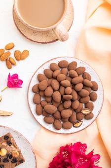 Миндаль в шоколадных драже на керамической тарелке и чашка кофе на белом фоне бетона и оранжевой льняной ткани. вид сверху, плоская планировка.