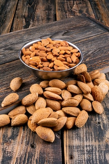 Almond in a iron bowl high angle view on a dark wooden table