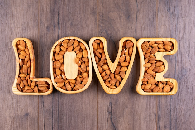 Almond in a love shaped plates flat lay on a wooden table