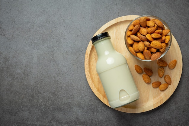 Almond milk in bottle with almond on dark background