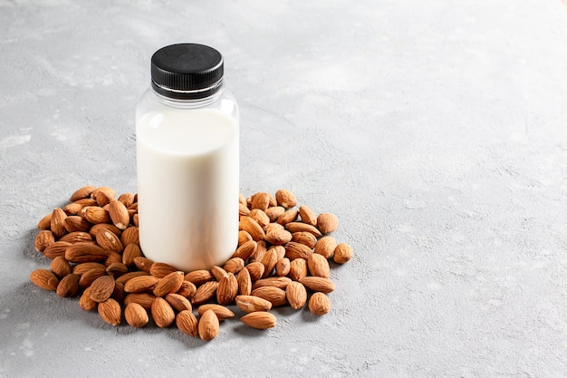 Almond milk in bottle with almonds on light gray background
