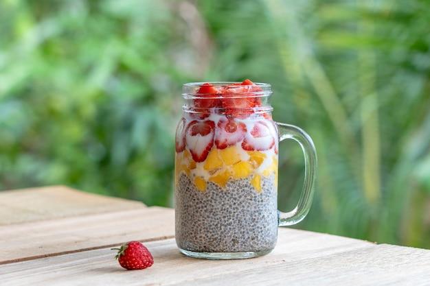 Пудинг чиа с миндальным молоком, свежей клубникой и манго в стеклянной кружке. веганский сырой завтрак. семена чиа и свежесрезанные фрукты и ягоды десерт, крупным планом