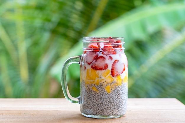 Пудинг чиа с миндальным молоком, свежей клубникой и манго в стеклянной кружке. веганский сырой завтрак. семена чиа и свежие нарезанные фрукты и ягоды десерт, крупным планом