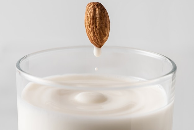 전체 너트에서 식물성 우유로 가득 찬 유리로 흐르는 아몬드 우유 방울