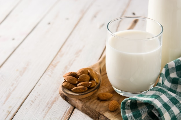 Almond milk in glass and bottle on white wooden table. copy space