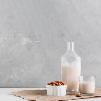 Almond milk in glass and bottle with almonds