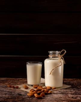 Миндальное молоко в бутылке и стакане, на темном винтажном деревянном фоне, с копией пространства
