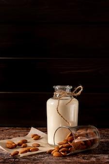 Миндальное молоко в бутылке, на темном винтажном деревянном фоне, с копией пространства
