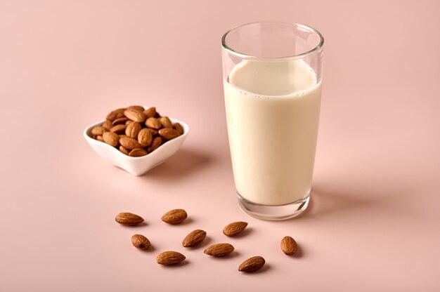 Миндальное молоко в стекле и семена орехов на фоне розового порошка крупным планом